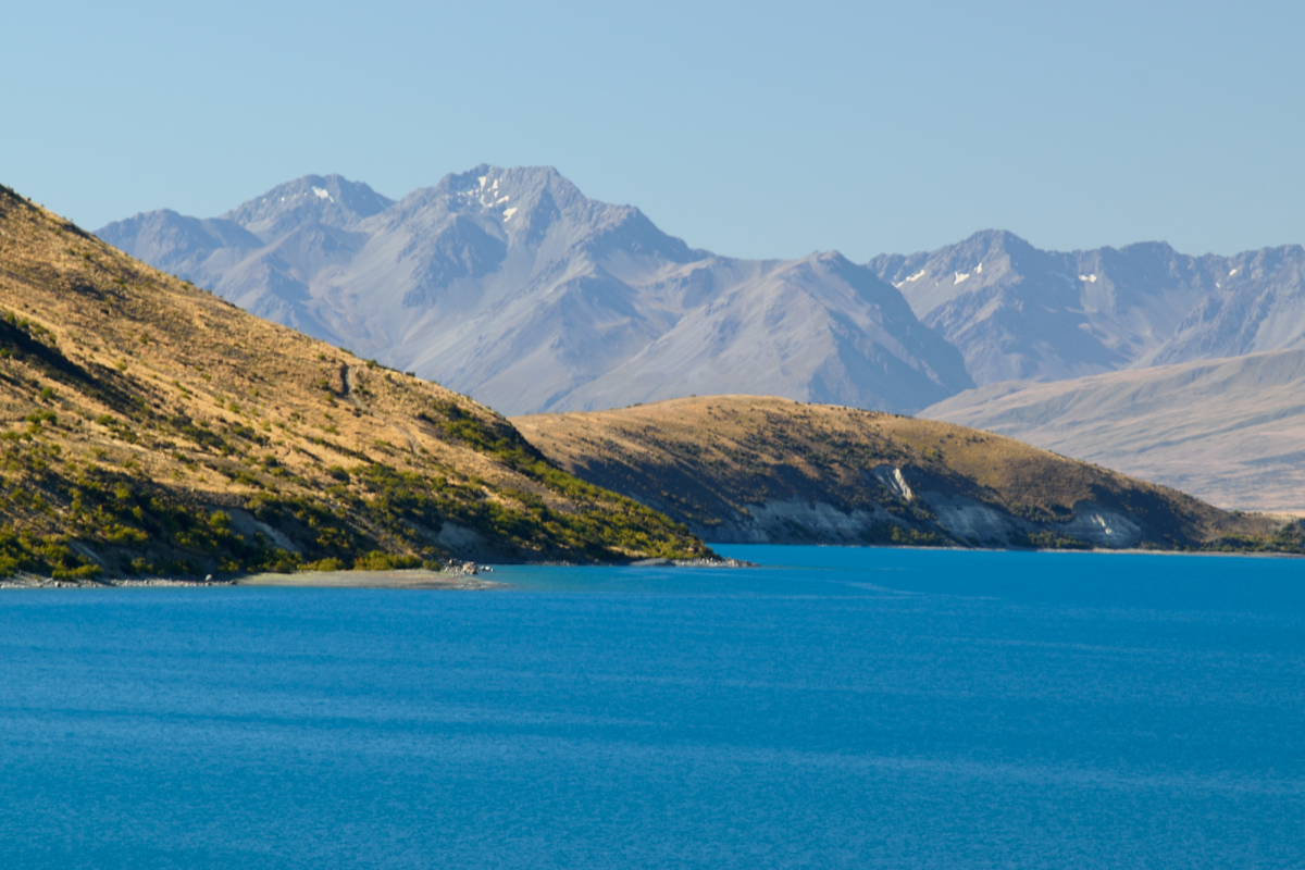 Lake Tekapo super blue water from glacier with Mackenzie base mountains in background